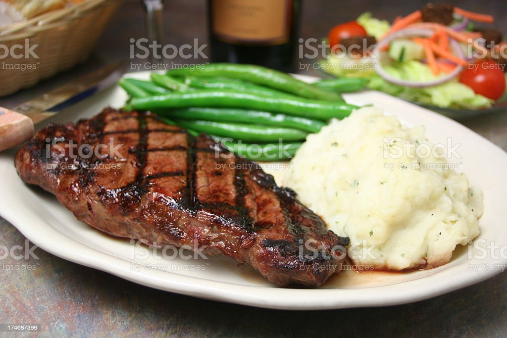Steak dinner with mashed potatoes and steamed green beans stock photo
