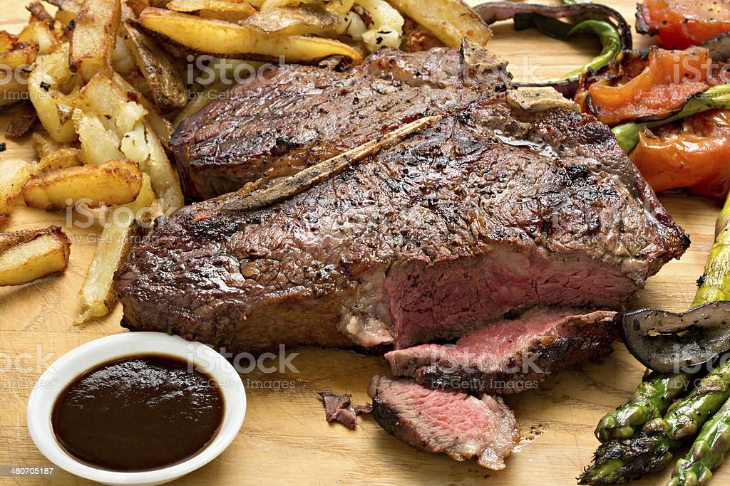 Steak, Fries, Vegetables And Sauce stock photo