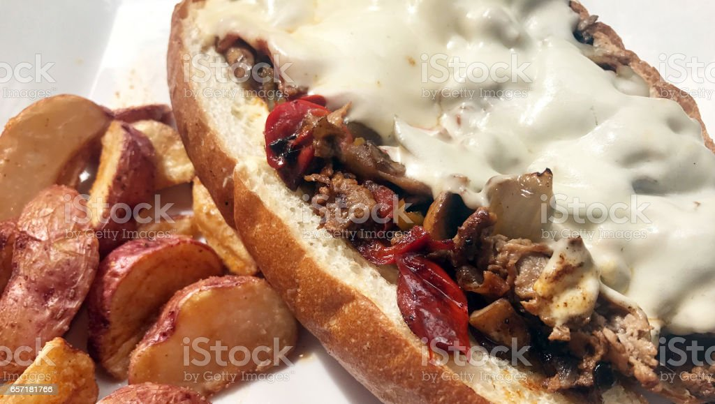 Steak hoagie sandwich with mushrooms, peppers and cheese. stock photo