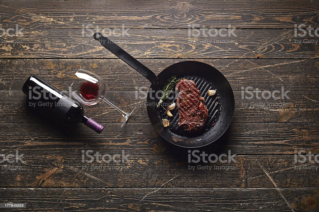 Steak in grill pan with wine bottle on old wood. stock photo