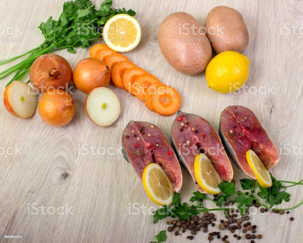 Steak of tuna, lemon, sea salt, pepper, fresh sprouts of greens. stock photo