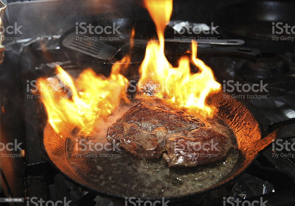 Steak on fire in frying pan royalty-free stock photo