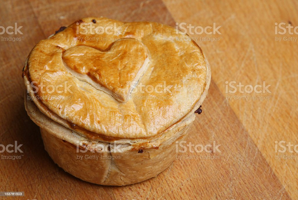 Steak pie on a wood table with a heart cooked into it stock photo