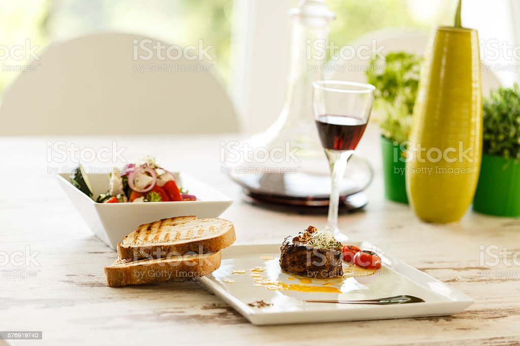 Steak, salad and wine for lunch stock photo