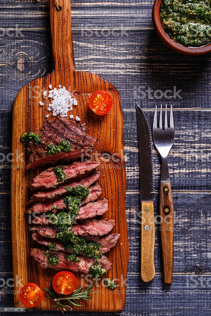 Steak served on a board with salsa verde. stock photo