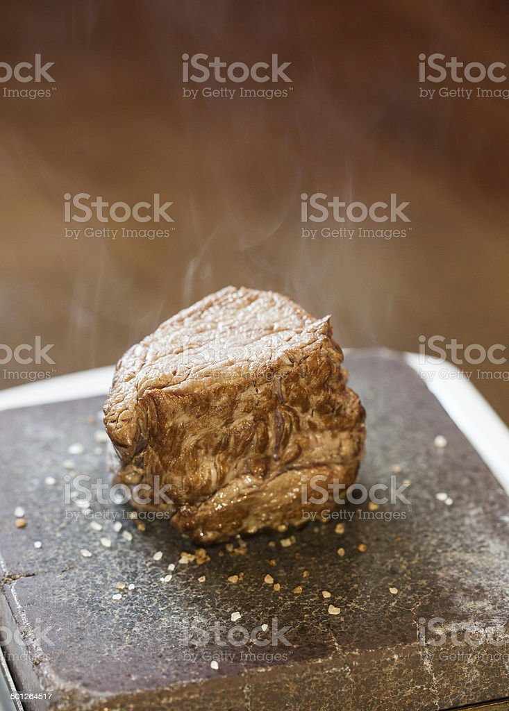 Steak sizzling on hot stone plate stock photo