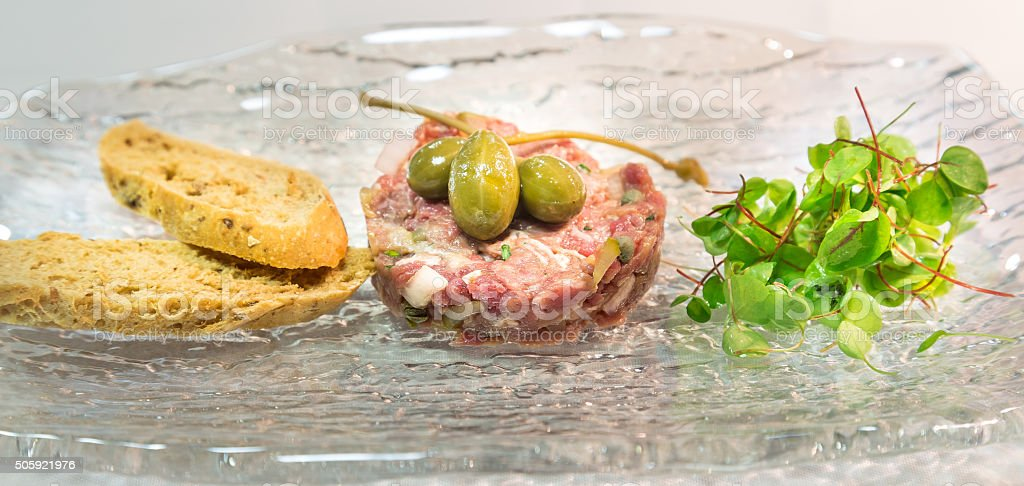 Steak Tartare with Capers, bread & salad leaves stock photo