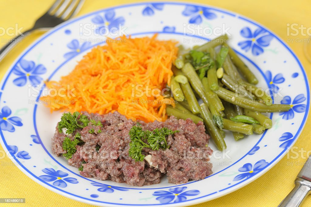Steak Tartare with shredded carrots and green beans stock photo