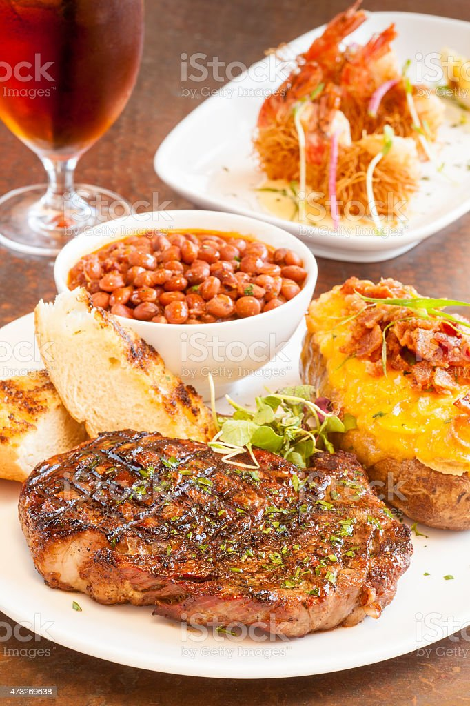 steak with baked potato, pinquito beans and grilled garlic bread stock photo