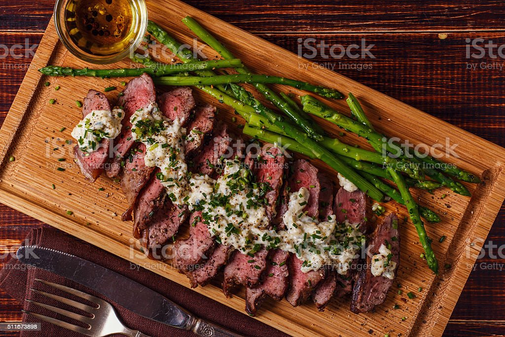 Steak with blue cheese sauce served with asparagus. stock photo