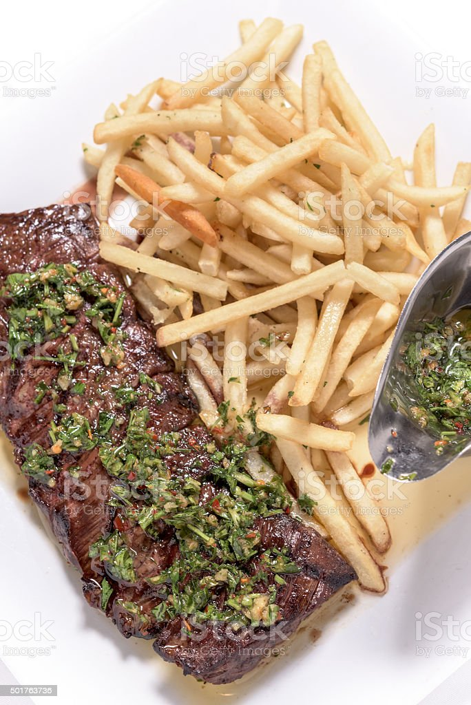 Steak with fries and chimichurri sauce stock photo