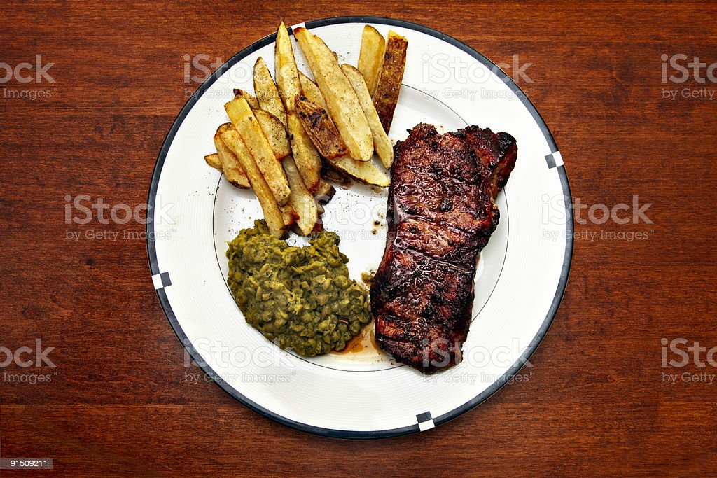 Steak with fries and mashed peas meal royalty-free stock photo