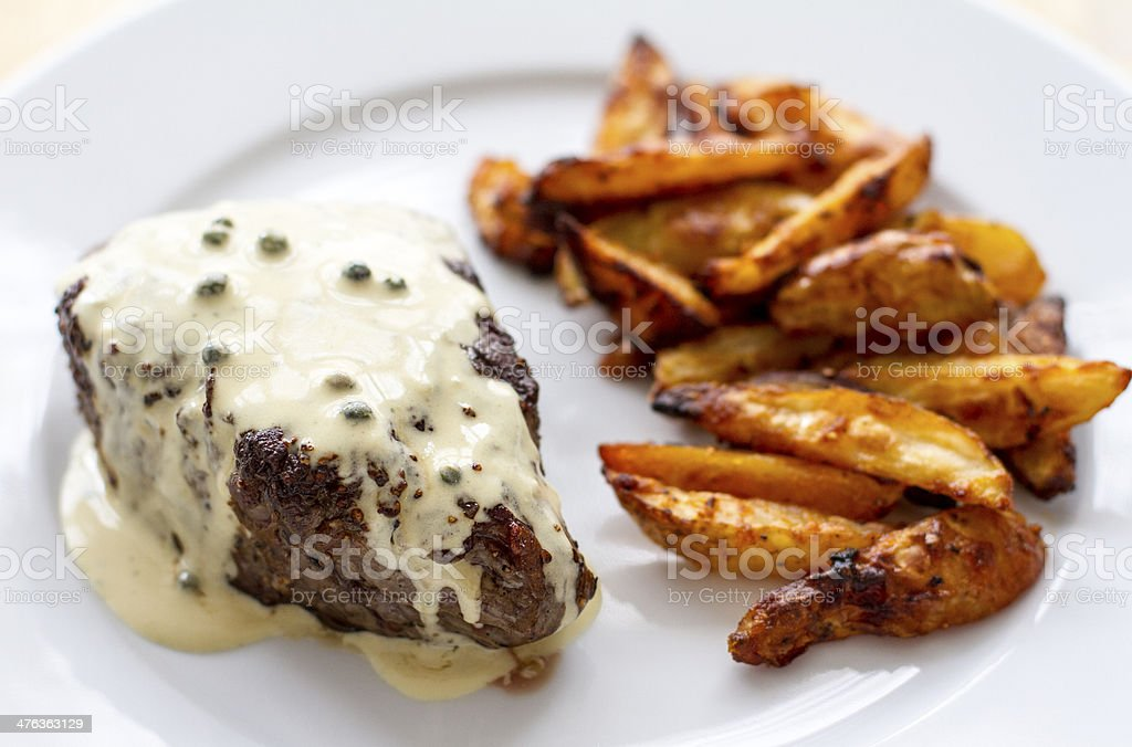Steak with green peppercorn sauce and fries stock photo