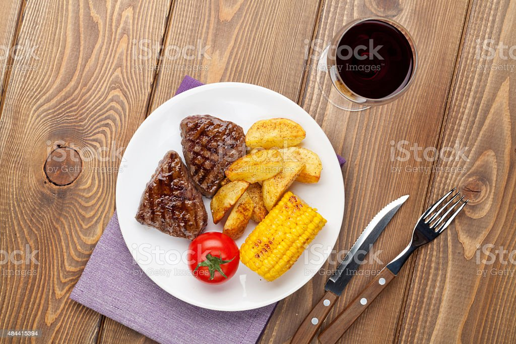 Steak with grilled potato, corn, salad and red wine stock photo