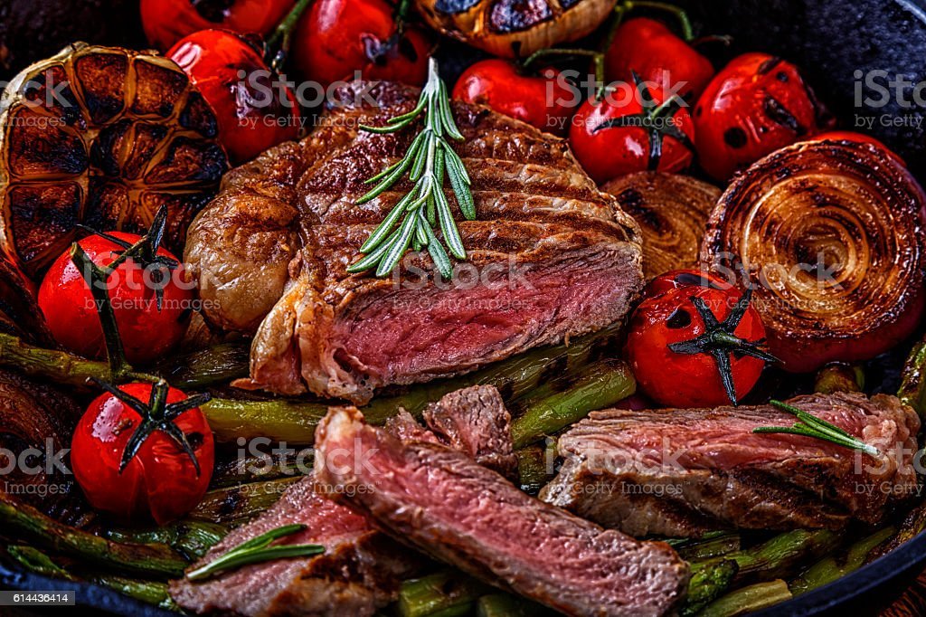 Steak with grilled vegetables in a frying pan. stock photo