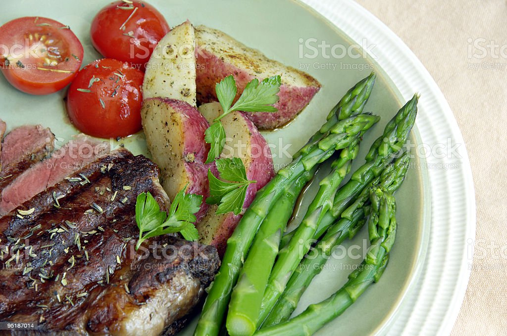 Steak with Potatoes, Tomatoes, and Asparagus royalty-free stock photo