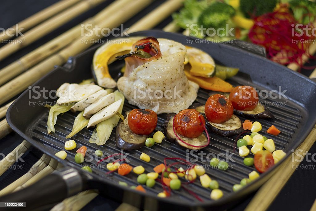 Steaks fish and vegetables in a pan. royalty-free stock photo