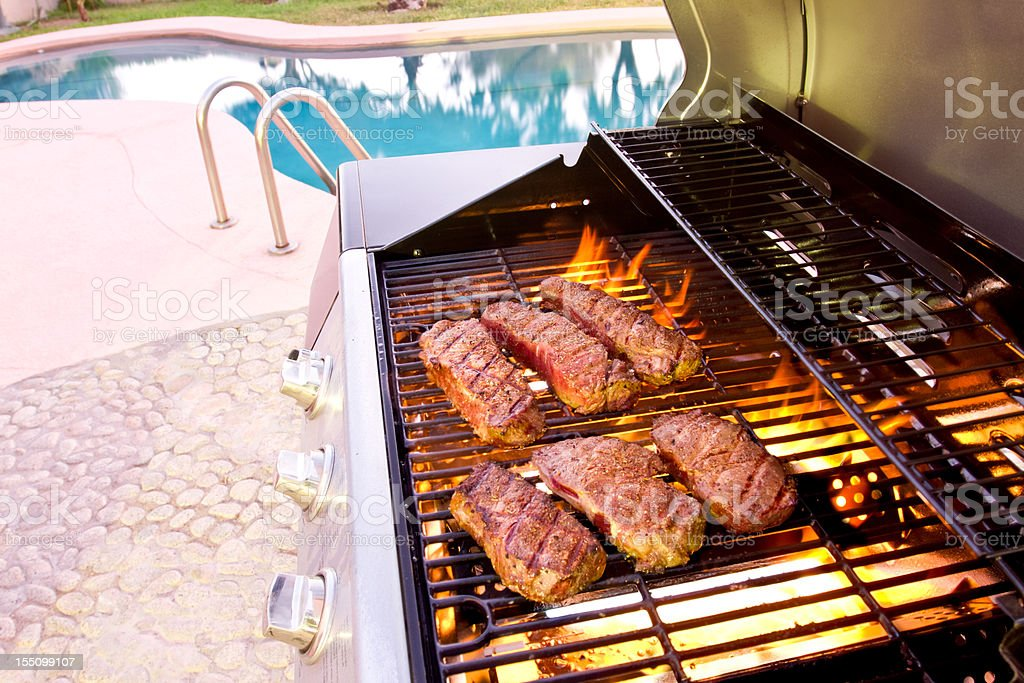 Steaks on Grill with Flames near Swimming Pool stock photo