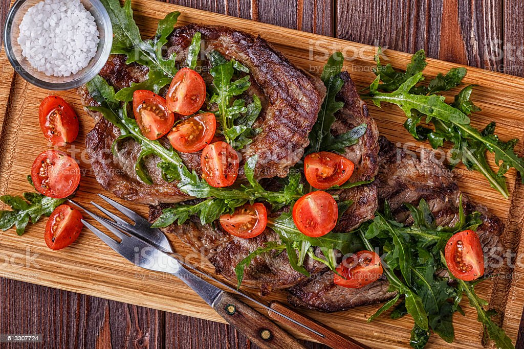 Steaks with arugula and tomatoes. stock photo