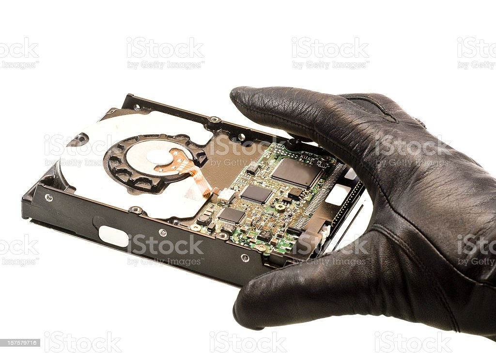 stealing data hand in black gloves taking harddrive stock photo