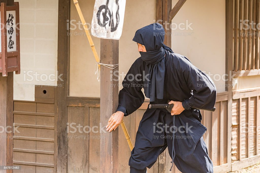 Stealthy Japanese Ninja Sneaking Through a Traditional Village stock photo