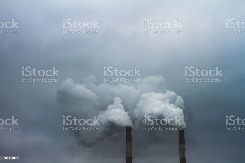 Steam and smoke is formed from boiler at susnset stock photo