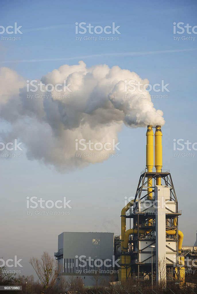 steam and yellow smoke stacks of incineration plant stock photo