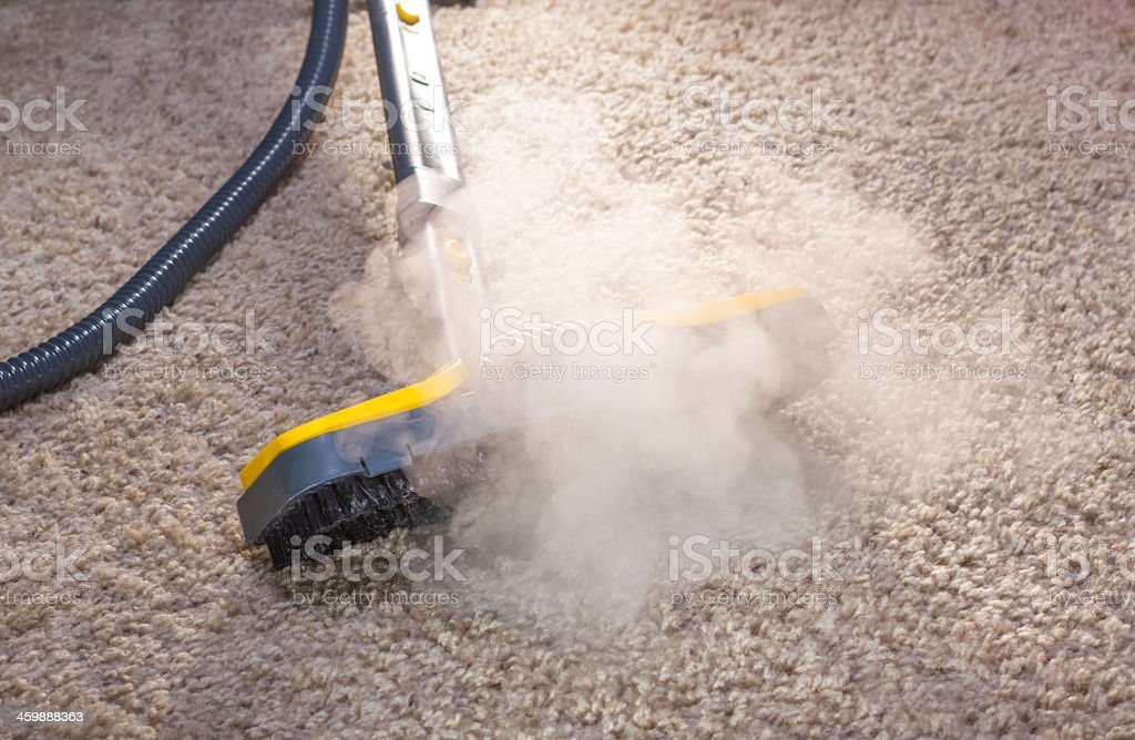 A steam cleaner in action cleaning a carpet stock photo