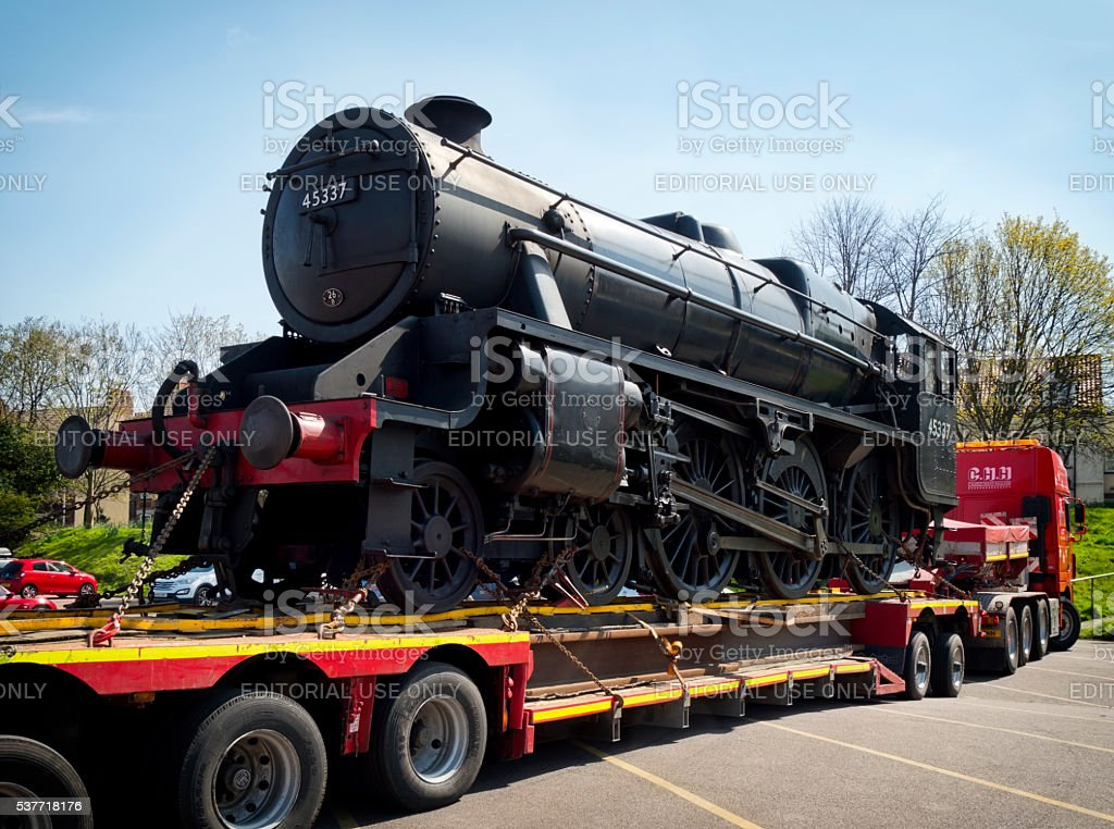 Steam engine being delivered by transporter lorry stock photo