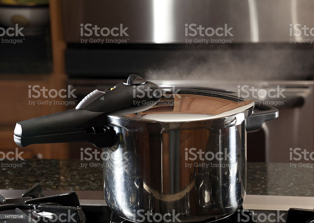 Steam escaping from new pressure cooker pot stock photo