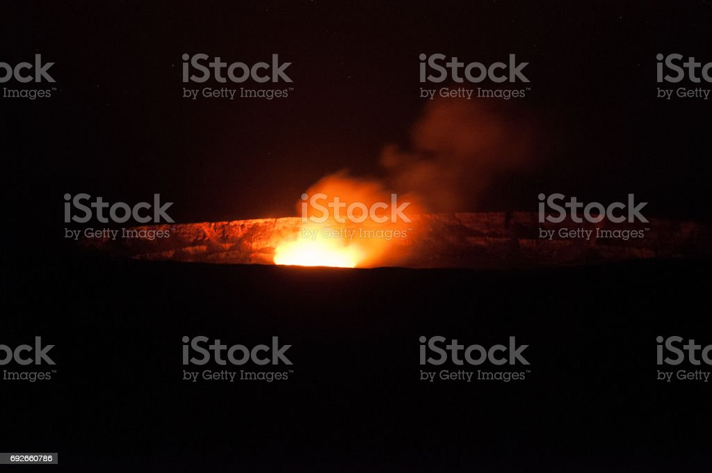 Steam from Kilauea's crater glows in the night. stock photo