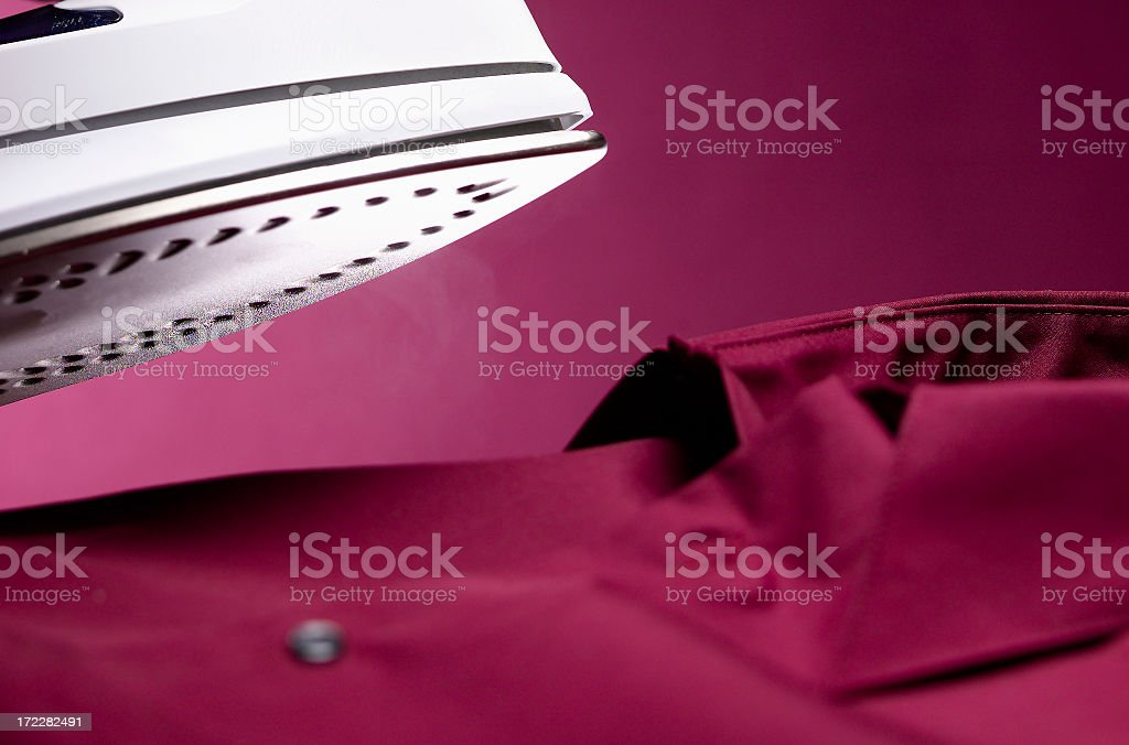 Steam iron close-up over button down shirt royalty-free stock photo