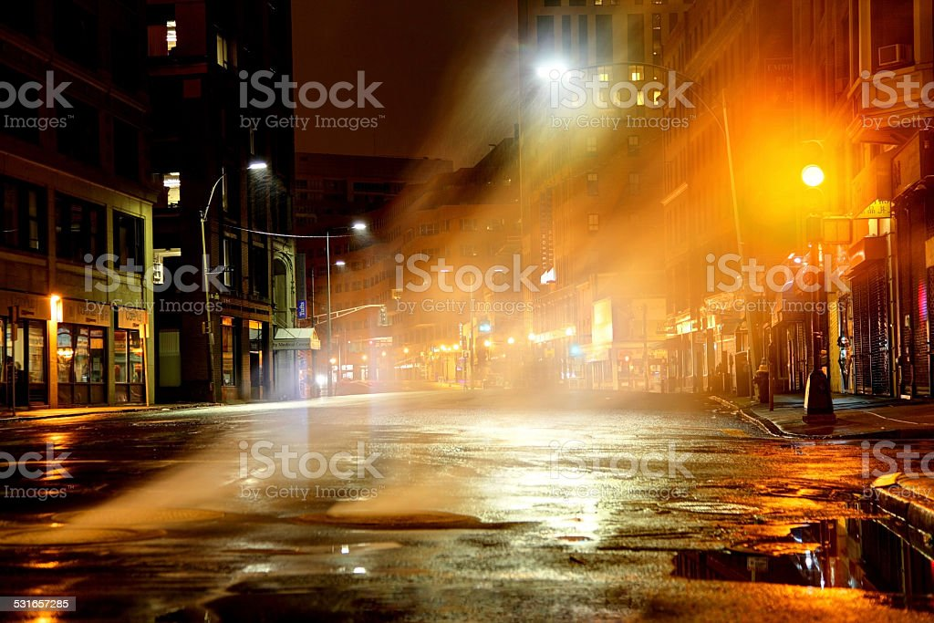 Steam rising from manhole cover on city street stock photo