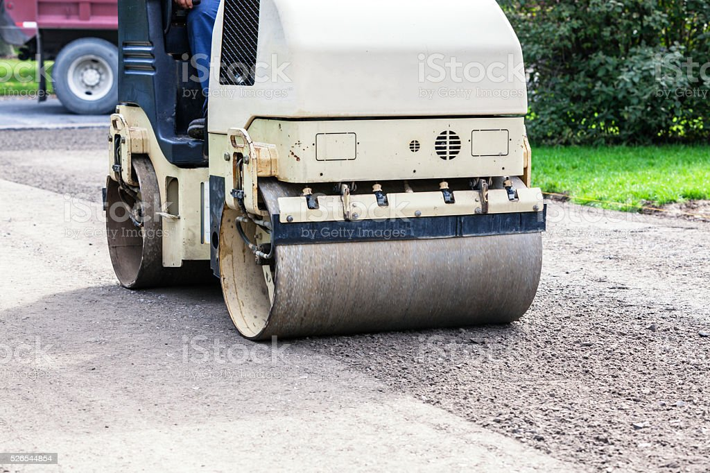 Steam Roller Leveling Crushed Stone Surface On New Driveway stock photo