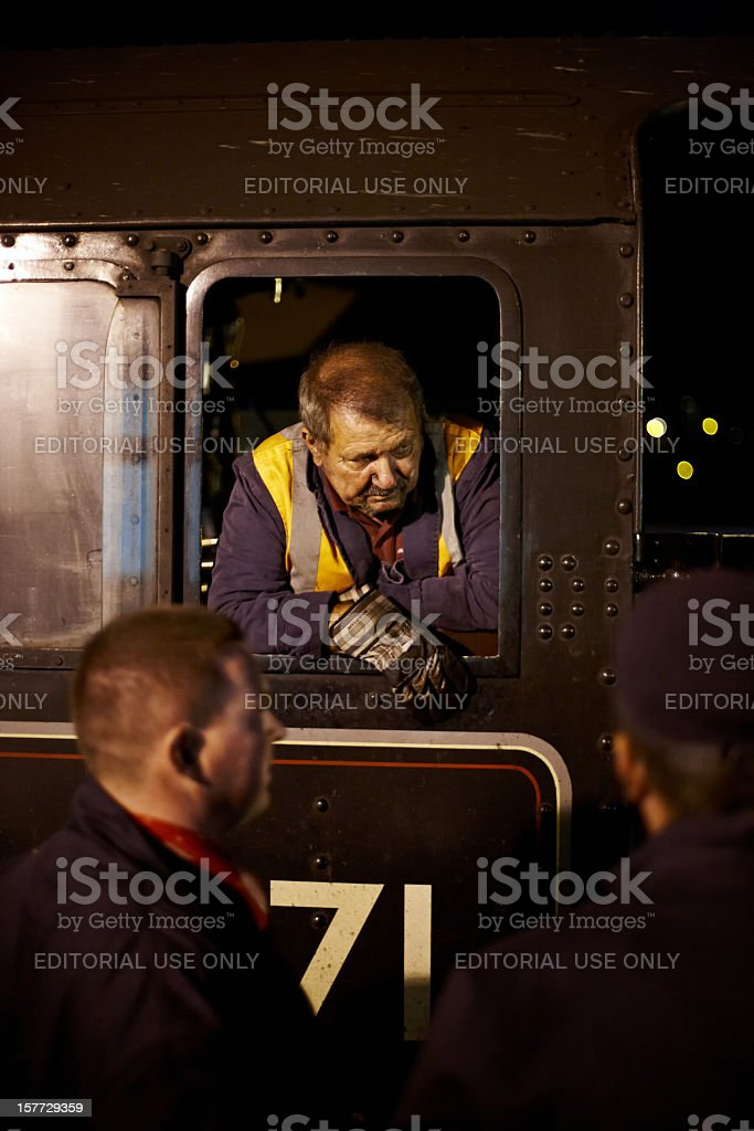 Steam train driver aboard footplate at night stock photo