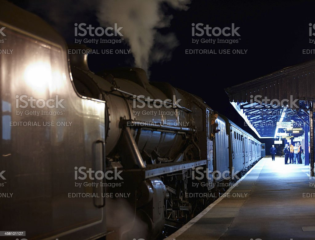 Steam train drivers aboard footplate at night stock photo