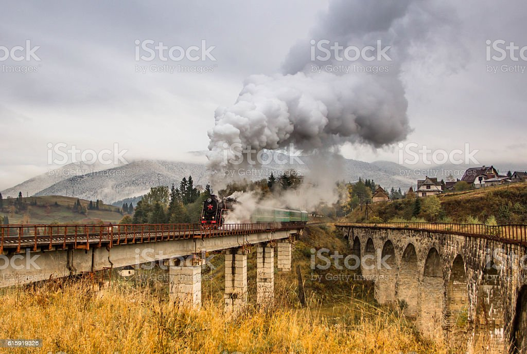 Steam train on the viaduct in the moyntains stock photo