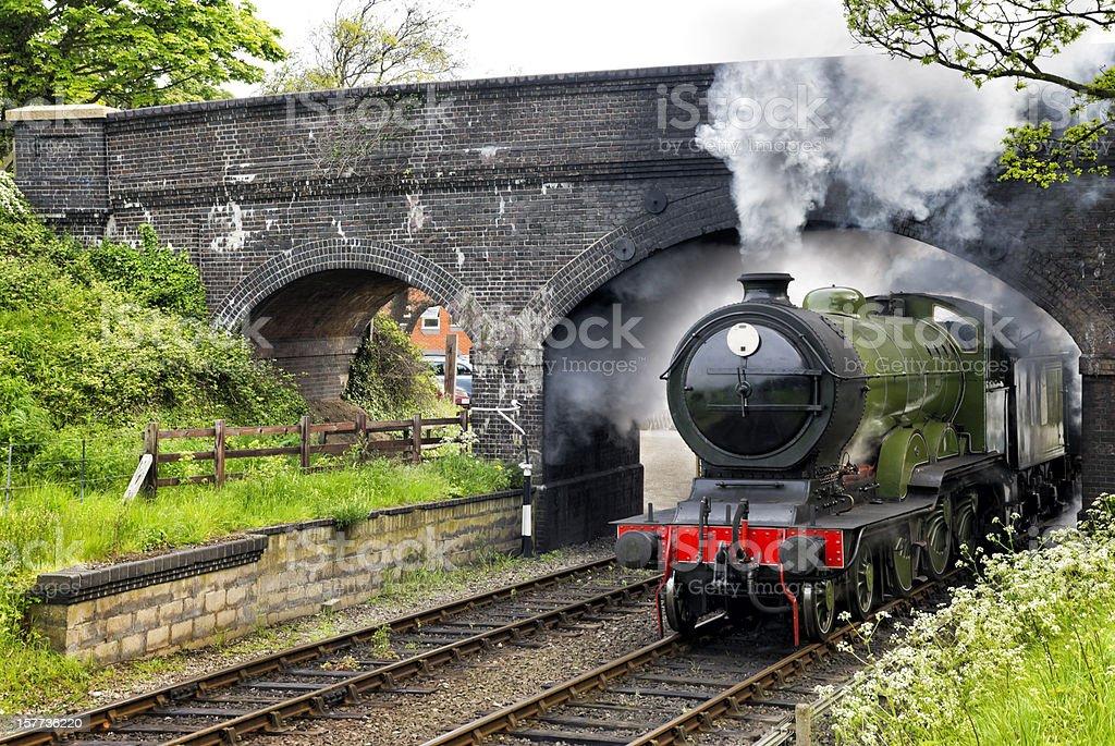 Steam train passing under a bridge stock photo