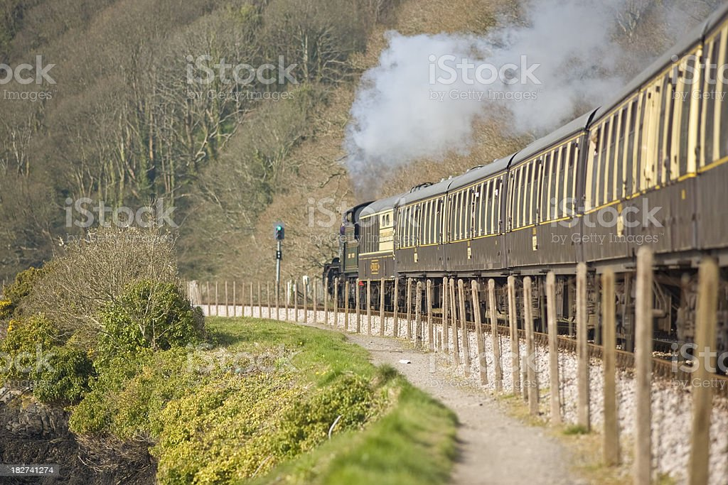 Steam train pulling carriages through English countryside stock photo