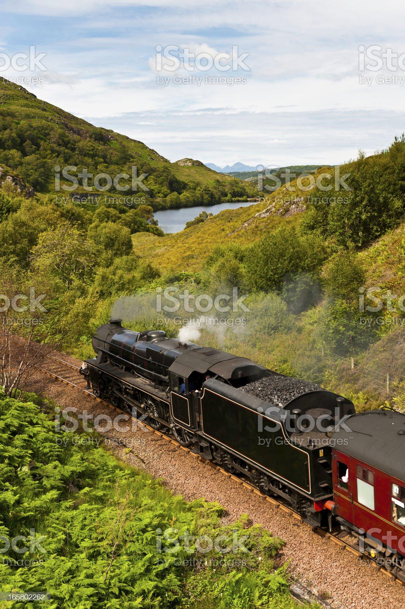 Steam train rushing through idyllic Highland mountain glen royalty-free stock photo