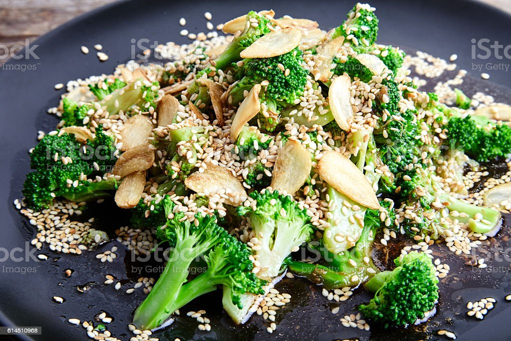 Steamed broccoli with garlic chips and sesame seeds stock photo