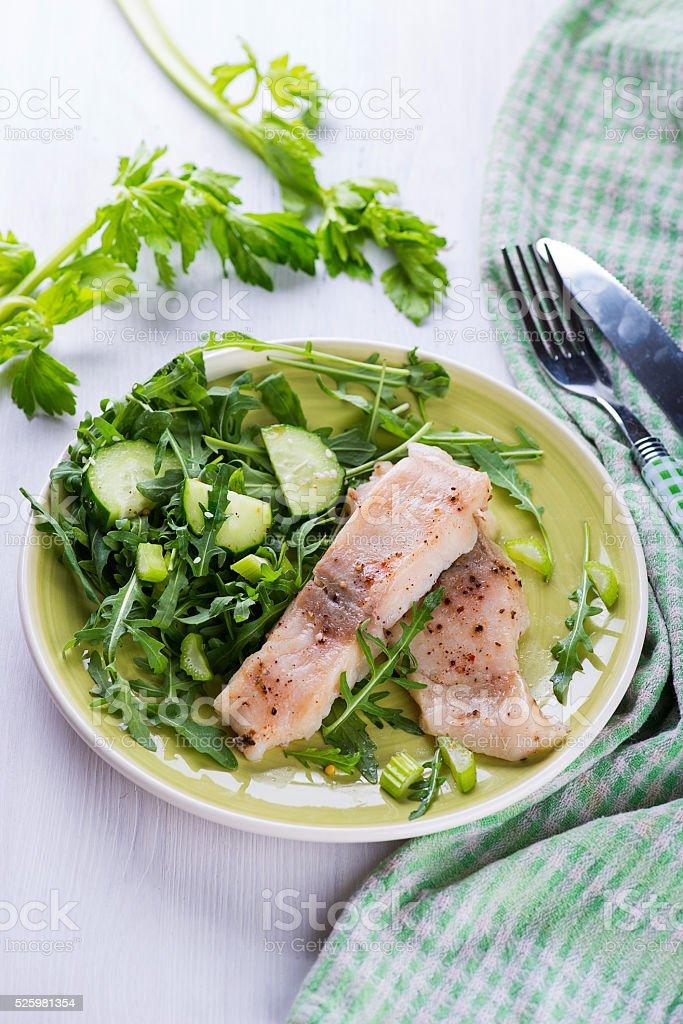 Steamed catfish filet with arugula salad stock photo