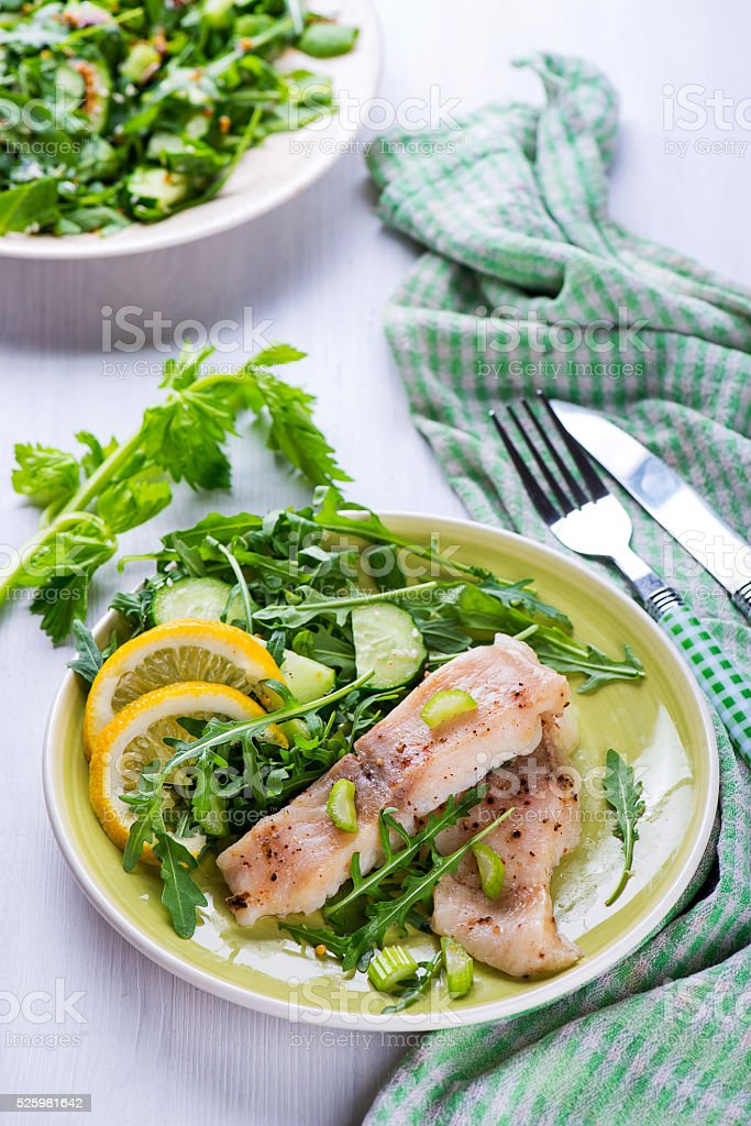 Steamed catfish filet with arugula salad stock photo