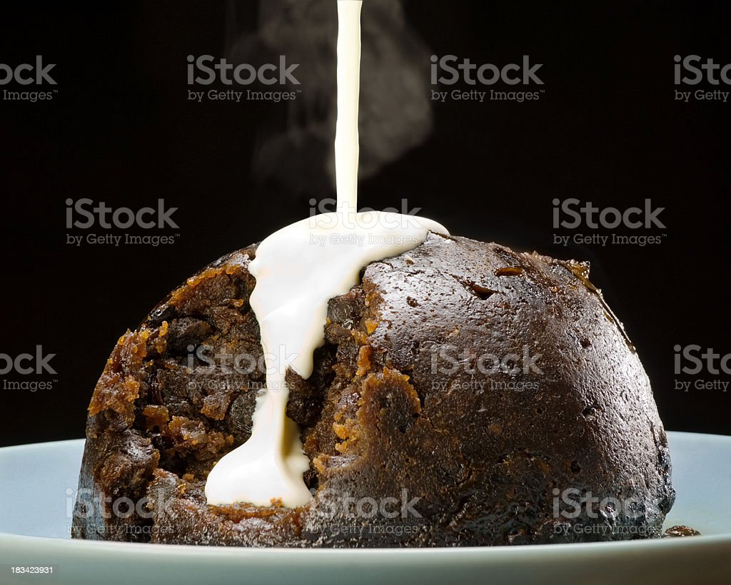 Steamed Christmas Pudding With White Sauce Dark Background royalty-free stock photo