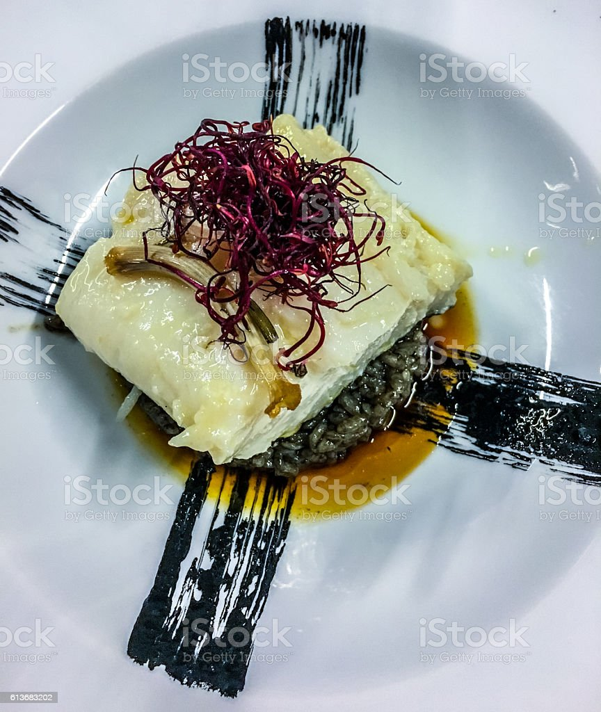 Steamed cod with black rice on a plate stock photo