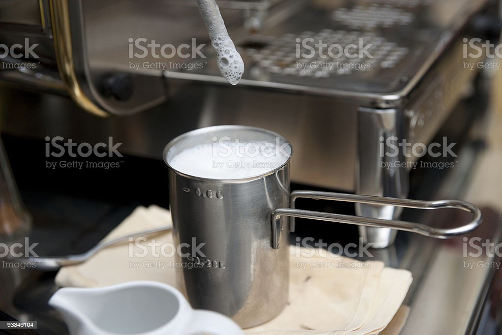 Steamed milk froth for preparing latte royalty-free stock photo