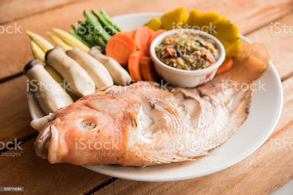 Steamed Nile tilapia  fish and vegetables, served with sauce on stock photo