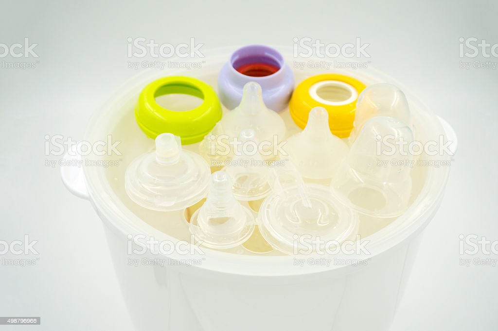 Steaming and sterilizing milk bottles for baby stock photo
