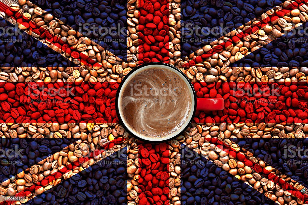 Steaming coffee cup on coffee grains and flag of UK stock photo