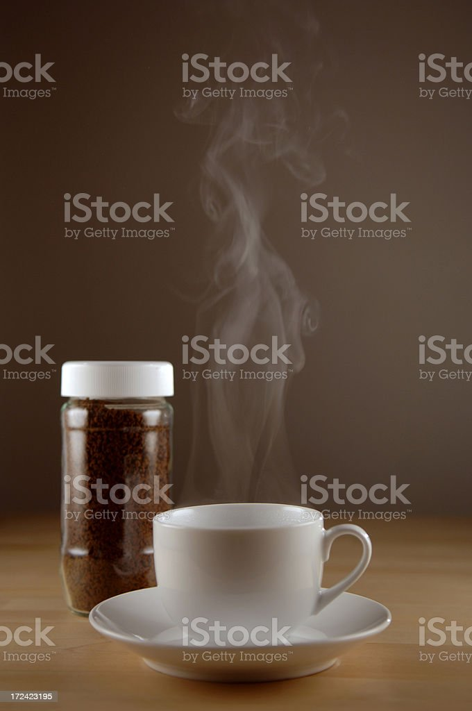 steaming cup of coffee and jar of instant coffee on table royalty-free stock photo